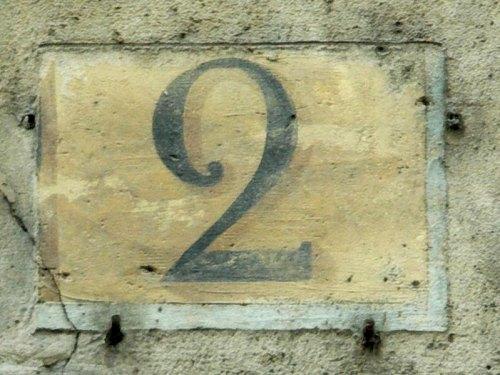 Numéro conforme à la réglementation de 1805 (chiffre noir sur fond ocre dans une rue perpendiculaire à la Seine)